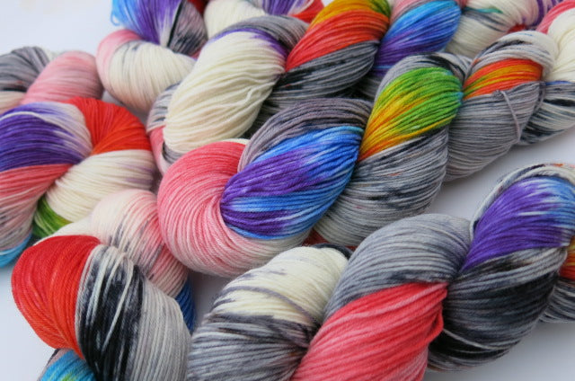 sock yarn skeins with rainbow colours and grey speckles on white and grey