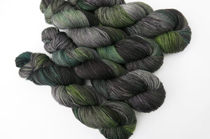 grey and black yarn skein with areas of emerald and spring green