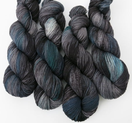grey and black yarn skein with areas of teal and blue