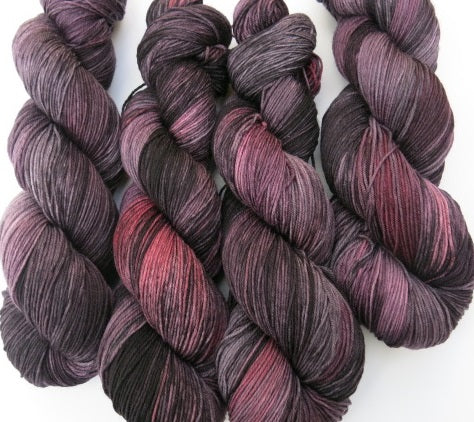 grey and black yarn skein with areas of red and pink