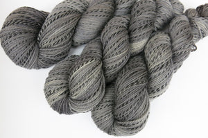 tonal grey yarn skeins with a black zebra stripe