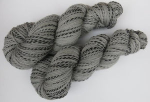light grey yarn skeins with a black stripe
