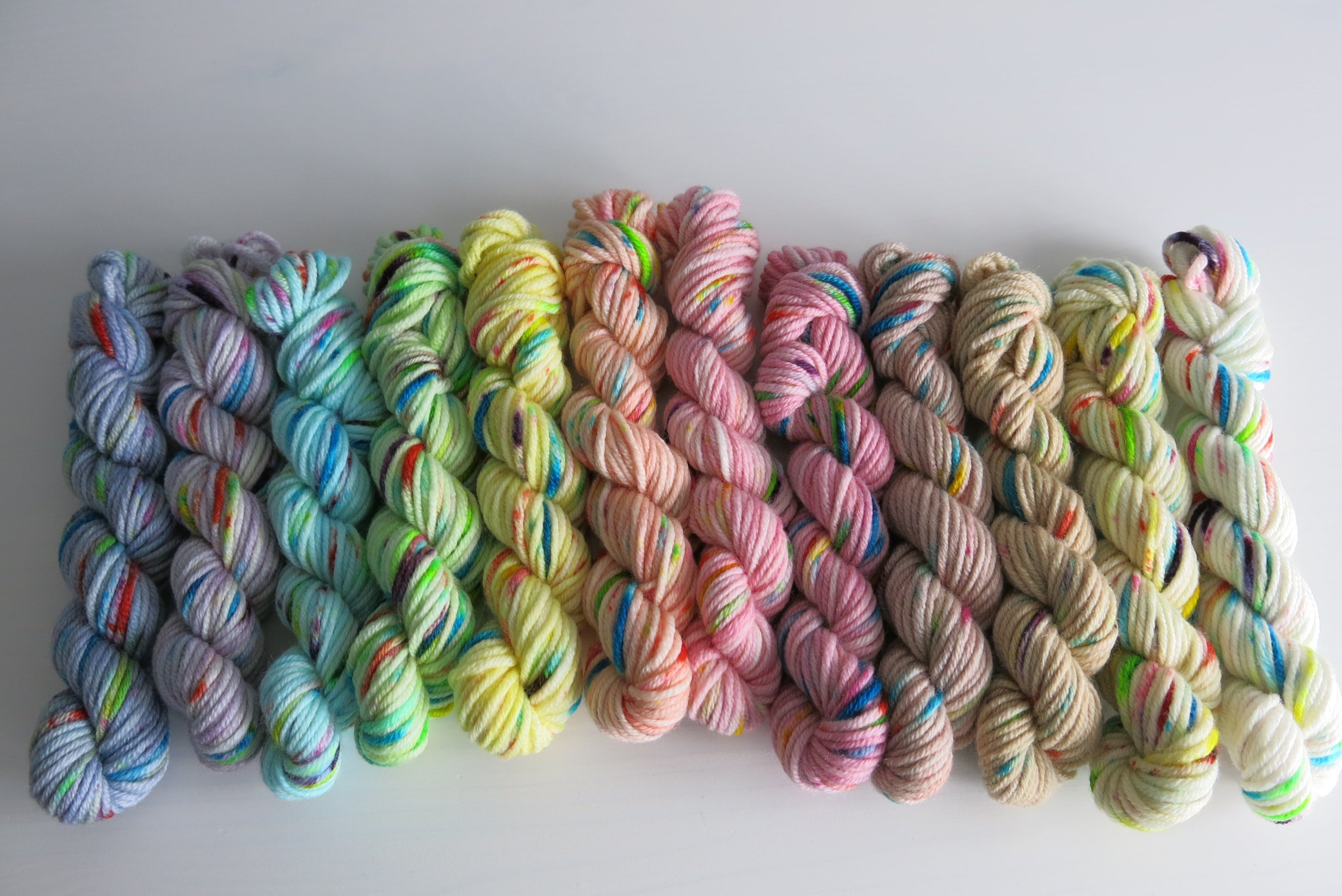 hand dyed pastel yarn mini skeins in a rainbow with speckles