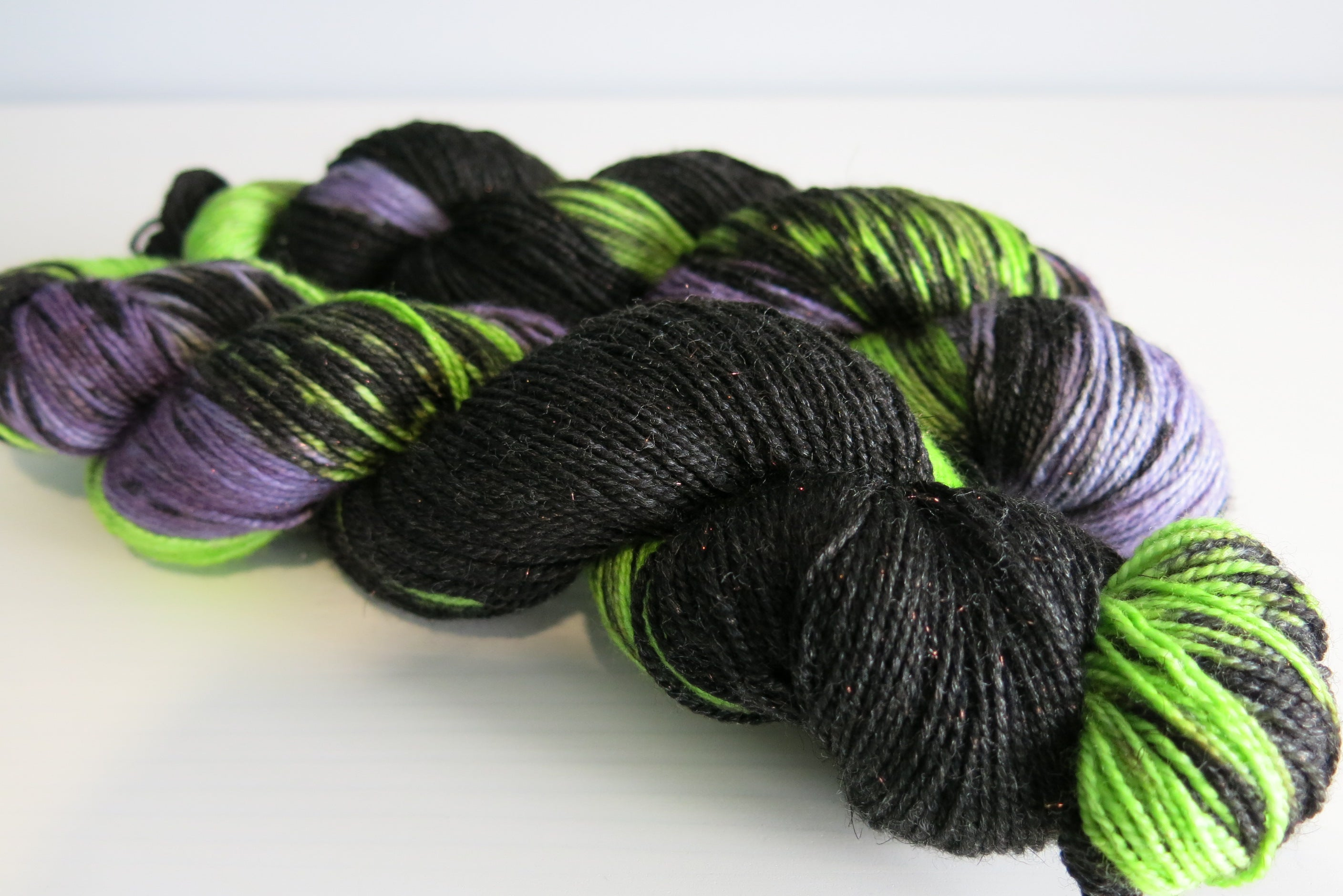 indie dyed purple and green sparkly merino sock yarn skein
