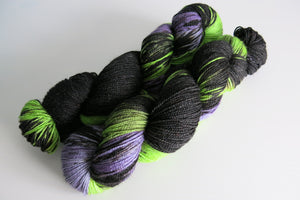 hand dyed purple and green with black sparkly merino sock yarn skein