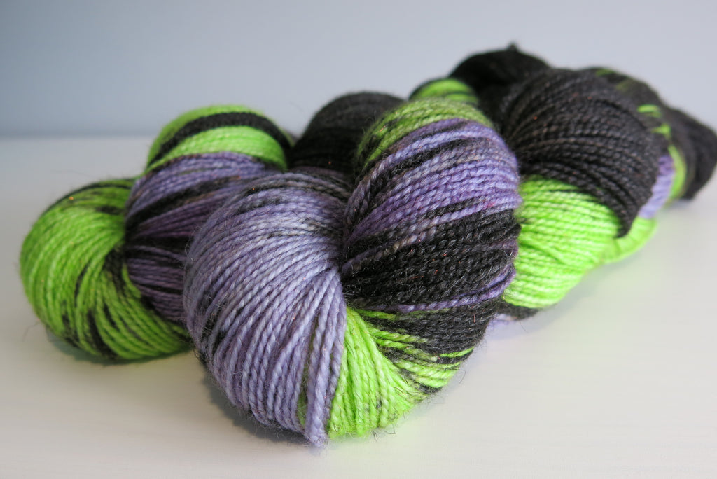 hand dyed purple and green sparkly merino sock yarn skein