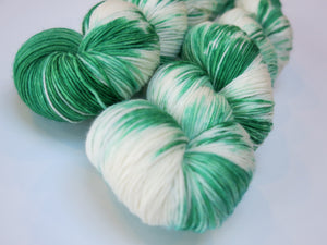 hand dyed green and white superwash sock yarn skein