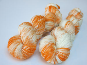 hand dyed orange and white superwash merino sock yarn