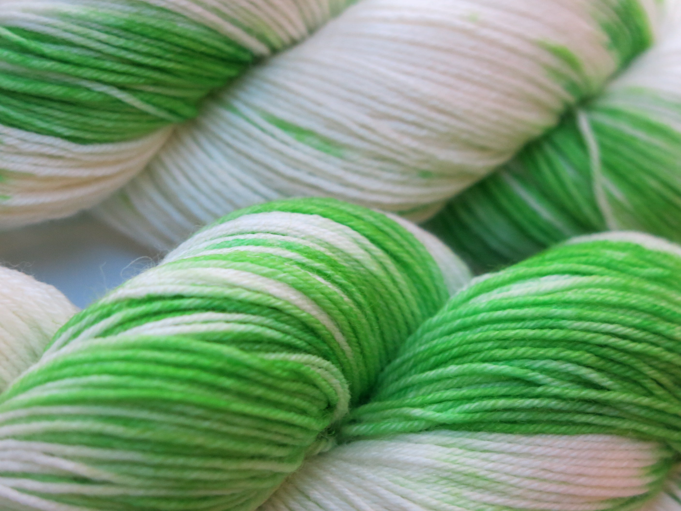hand dyed green and white superwash sock yarn skeins