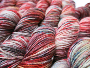red and blue speckled 8 ply merino yarn skeins
