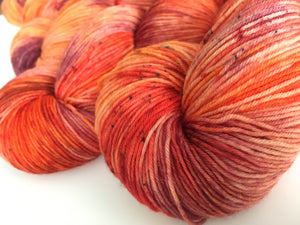 kraken uv reactibe orange speckled sock yarn skein