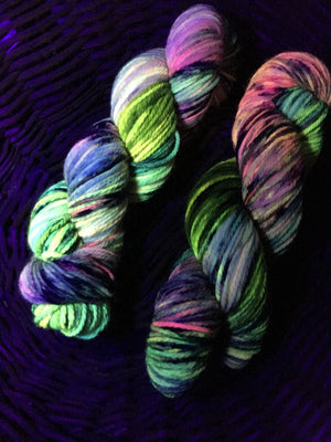 uv reactive yellow and pink aran yarn under black light