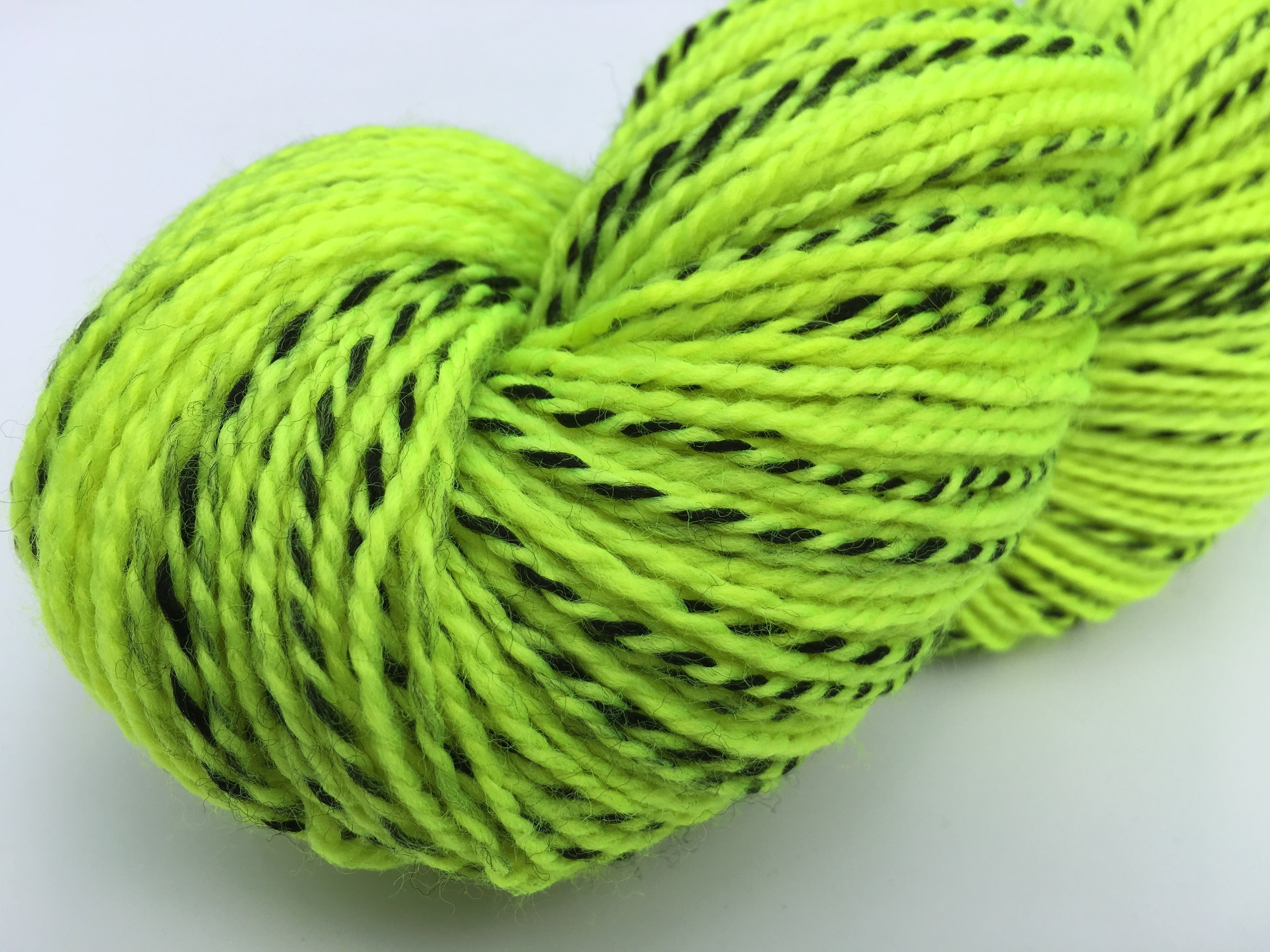 uv reactive neon highlighter yellow green sock yarn with a black zebra stripe