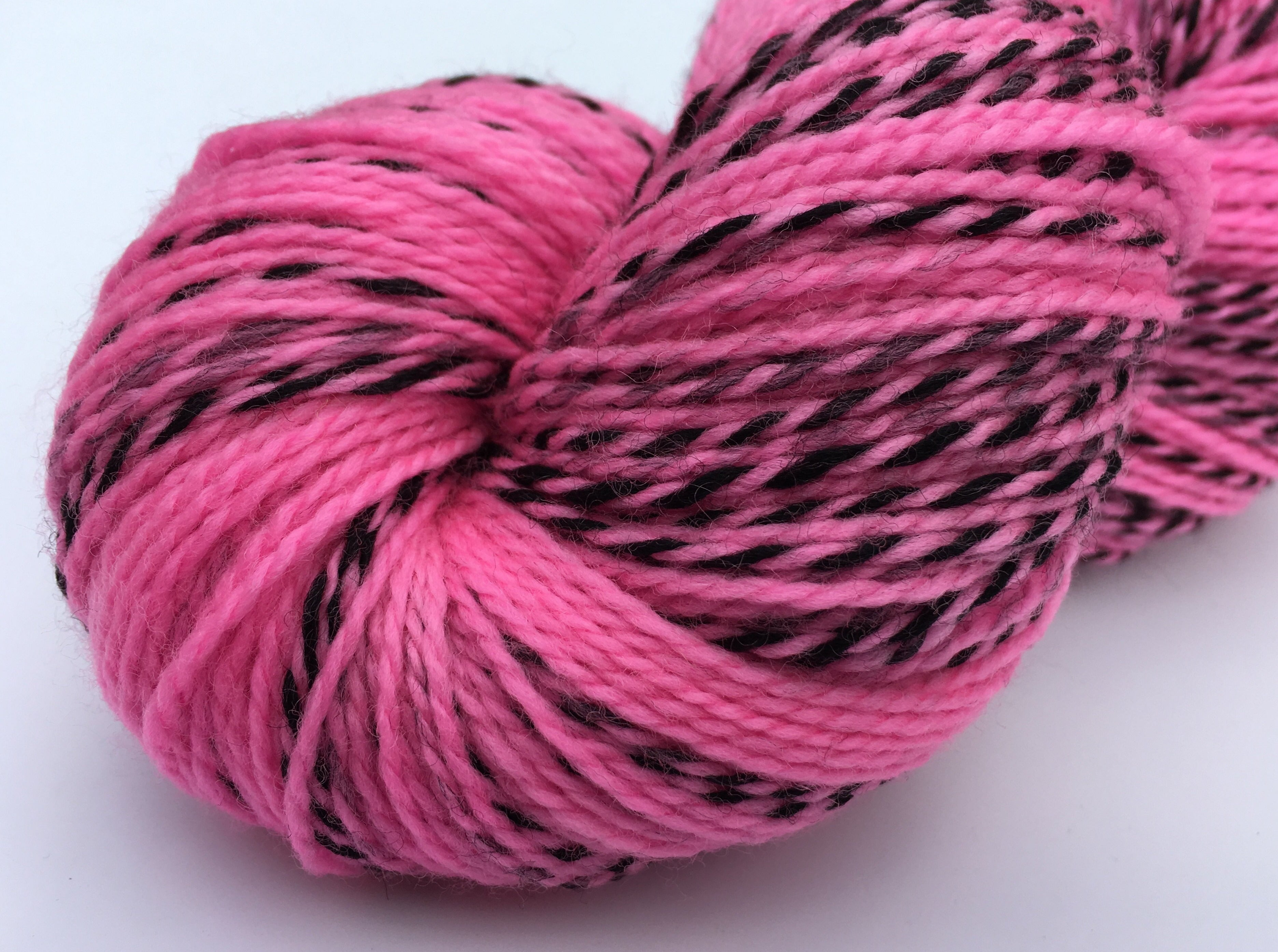 uv reactive neon cotton candy pink sock yarn with a black zebra stripe