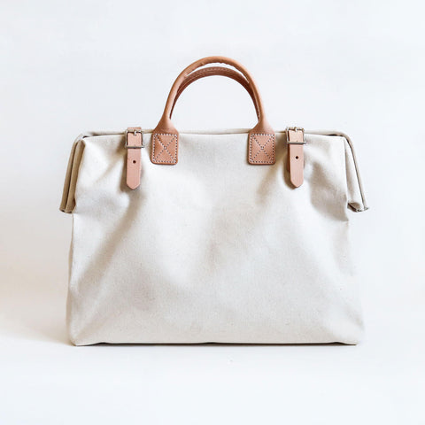 A white cotton canvas handbag with leather belted buckles with quality leather handles in between