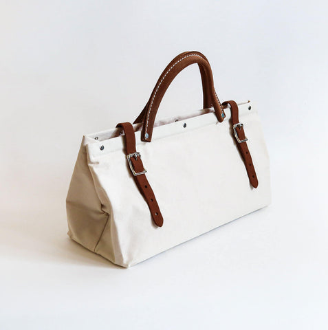 A medium sized white cotton canvas handbag with two brown suede leather belt buckle closure with a brown suede leather handle in between with white stitching