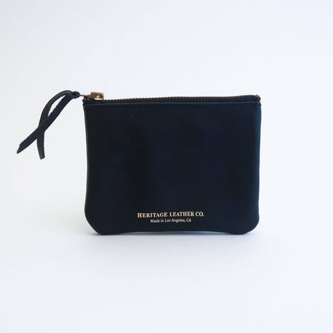 A black leather wallet with a single zip closure with gold foil printed Heritage Leather logo on the front