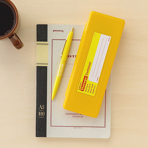 a desktop view of a yellow pen case made of plastic with write-in sticker next to a yellow ball-point pen laying on top pf a notebook that reads penco and A5