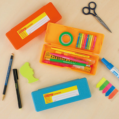 desktop view of penco storage container pen case in orange, yellow and light blue showcasing color variations and open and closed cases. open pen case includes pens, pencil, masking tape and ruler surrounded by Penco prime timber mechanical pencil as well as blue glue and scissors.