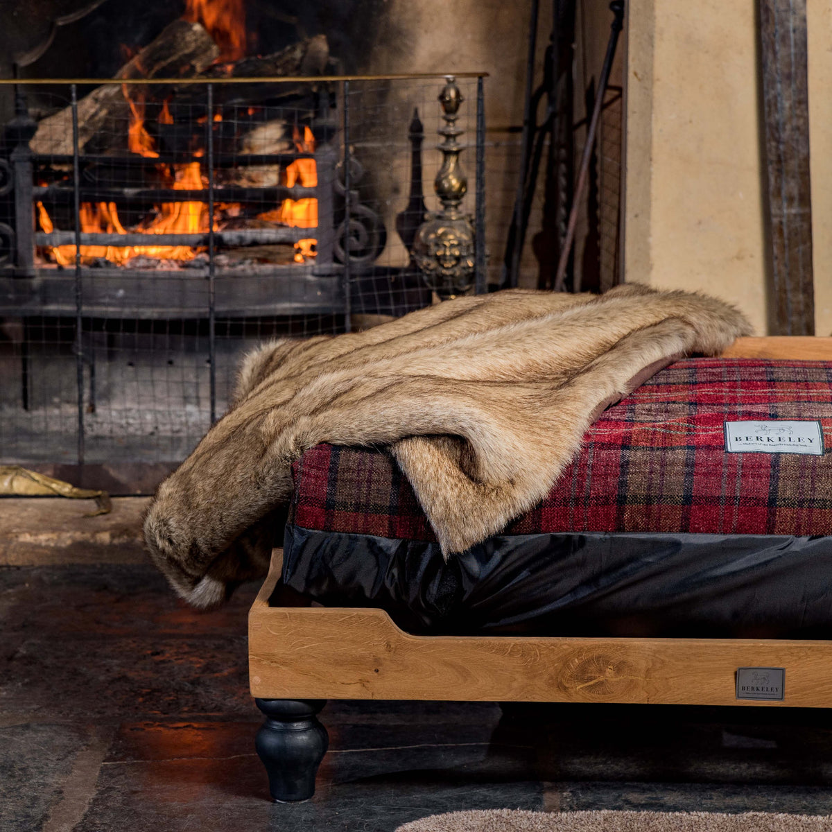 Raised wooden dog bed with tartan mattress and faux fur throw