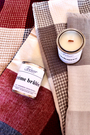 Cashmere scented wood-wick hand poured candle and gray/beige plaid and waffle knit blanket scarf. Creme Brûlée scented wood-wick candle and red/navy plaid and waffle knit blanket scarf.