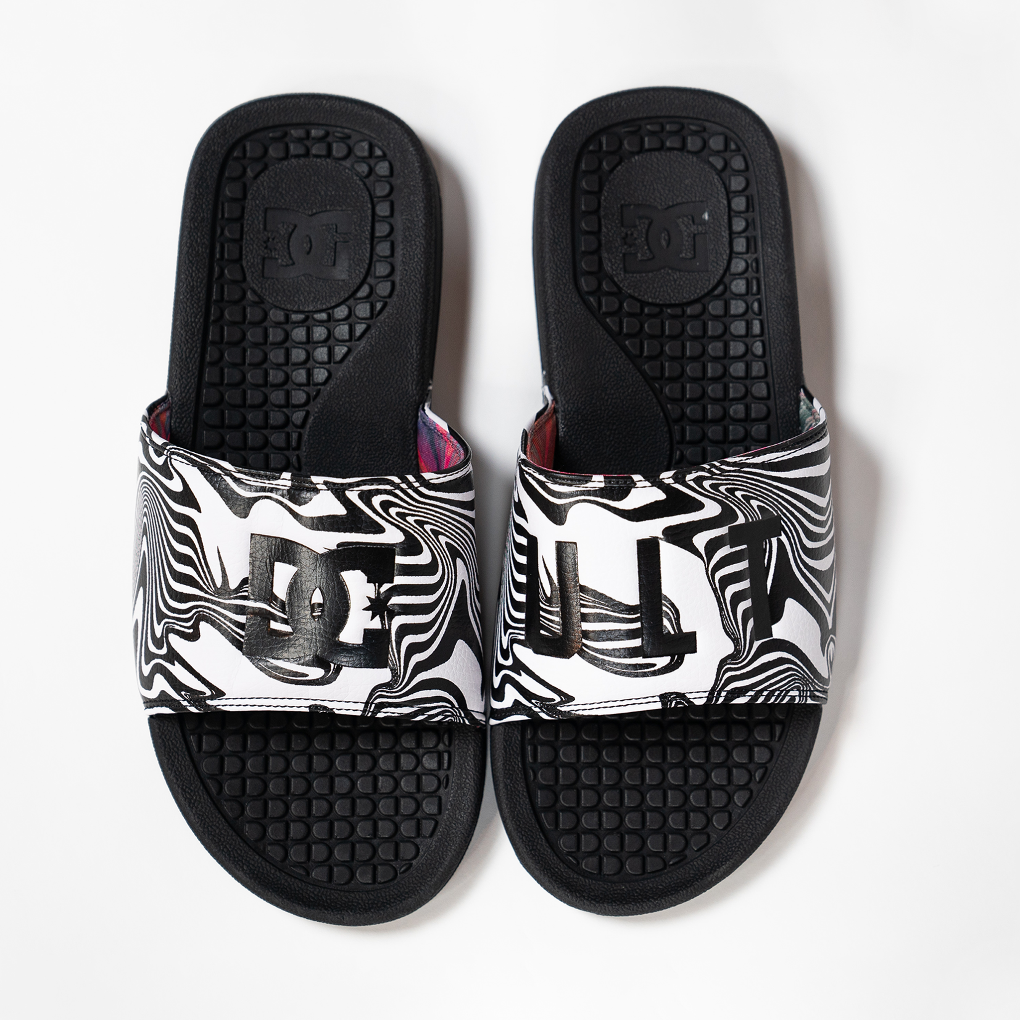 A pair of slide style sandals on white background. Black rubber soled with the strap being black and white. Strap features a black and white swirl design with the DC Shoes logo on the right shoe and ULT on the left shoe.