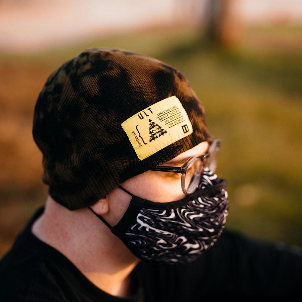 Model facing to the right wearing a tie dye beanie with a neon yellow label, glasses, and a mask. Mask features a black and white swirl design.