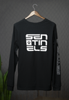 "Photo features a black long sleeve tee with a large rectangular white print. The white print has ""Sentinels"" spelled on the wearer's left chest. The rest of the print is small thin wave like lines with text at the bottom."