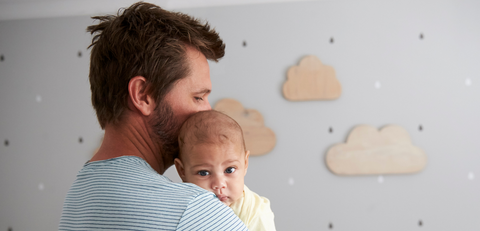 Baby hold by dad in nursery room
