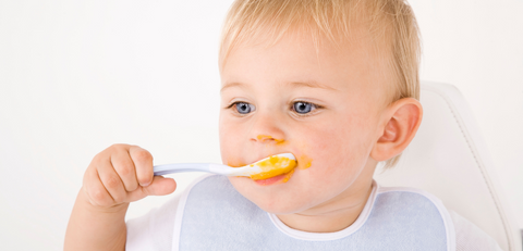 baby holding a spoon