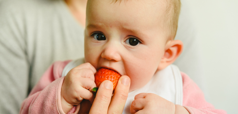unhappy baby eating a strawberry