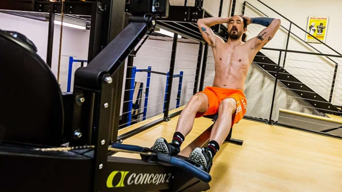 Steve Aoki works out in his home gym with an eSmartr sleeve on his arm.