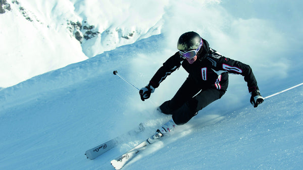 A man controls the speed of his descent  down the slopes.