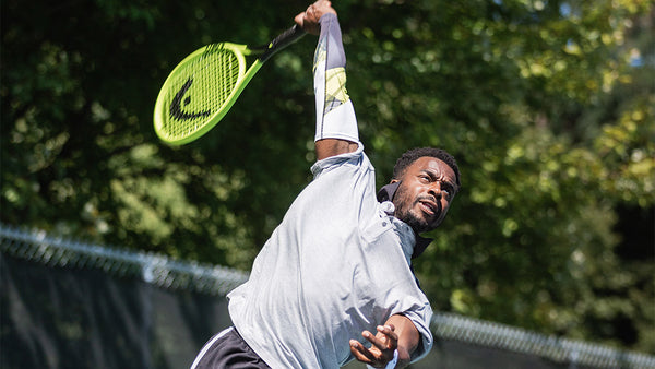 A player practices drills for tennis fitness using his eSmartr/HEAD sleeve and HEAD racket.