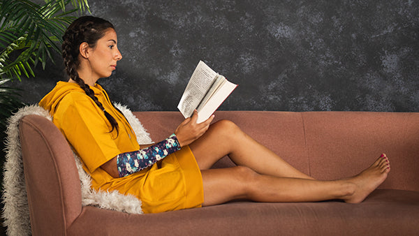 A young woman reads to relax with an eSmartr sleeve on to help her focus.