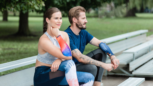 A man and woman sit to rest on some bleachers following a core workout.