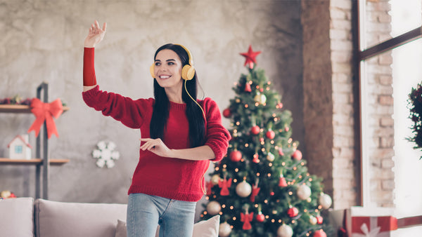A woman listens to music at Christmastime; a red eSmartr sleeve matches her sweater and decorations.