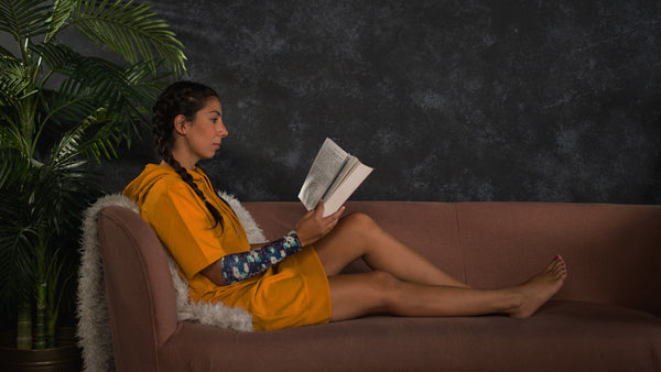 A young woman reads before bed, with an eSmartr sleeve on her arm.