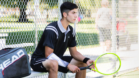 A young man prepares for a tennis drill with an eSmartr/HEAD sleeve on his arm.