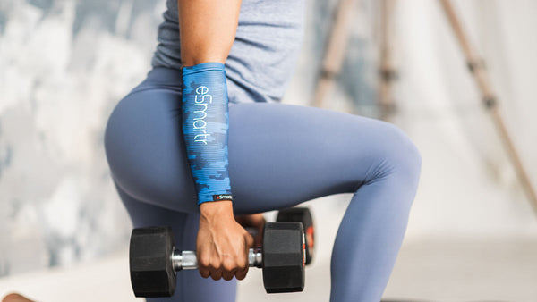 A woman lifts weights with a compression sleeve on her arm.