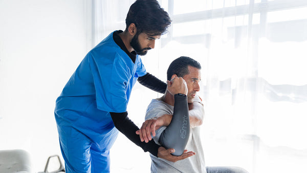 A doctor tests a patient's range of motion as he wears a smart compression sleeve from eSmartr