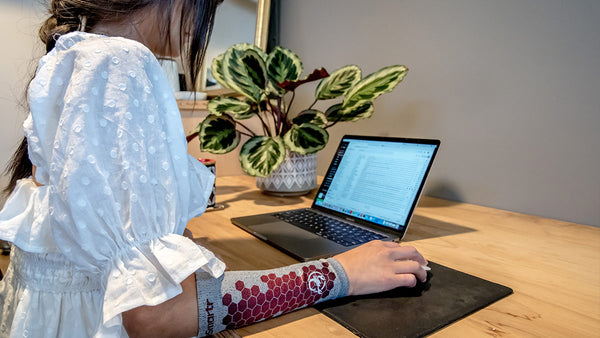 A woman works on a laptop, with an eSmartr scorpion sleeve on her arm.