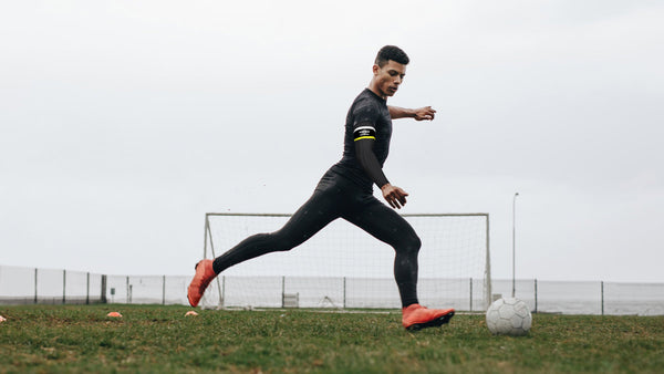 A man plays soccer with an eSmartr x Umbro smart compression sleeve on his arm.