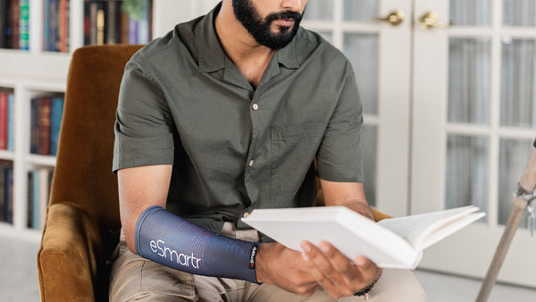 A man finds time to read a book with an eSmartr sleeve on his arm.