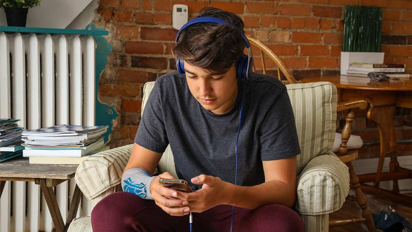 A young man listens to music on his phone, an eSmartr smart compression sleeve on his arm.