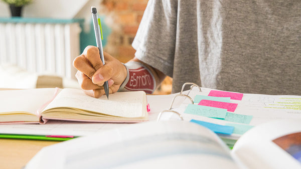 A young woman takes notes out of a notebook with sticky notes and organizational tools utilized; she has an eSmartr smart compression sleeve on her arm.