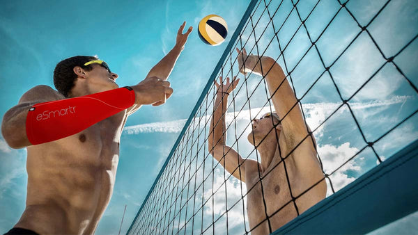 Two men reach for a volleyball over a net; one of them is wearing an eSmartr smart compression sleeve in the POWER style.