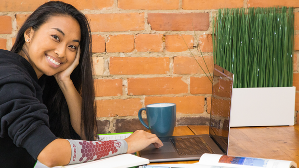 A young woman wears an eSmartr sleeve to improve her focus on work.