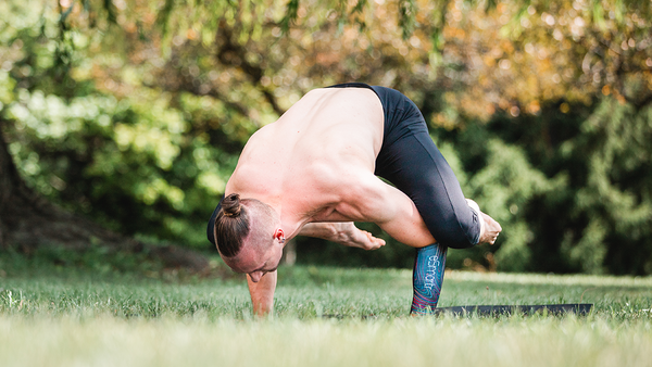 A man practices yoga and wears an eSmartr sleeve to boost his focus.