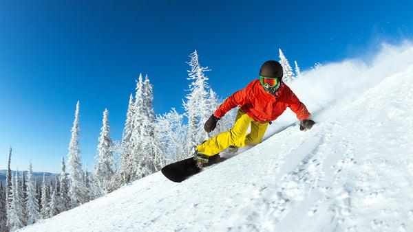 A snowboarder shreds on a downhill slope.